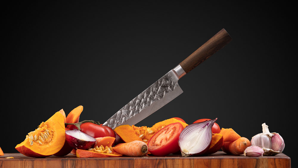 BARE Cookware knife over pile of orange vegetables